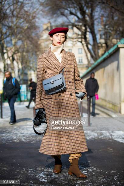 Norelle Weng wearing a checked long coat a french hat and a Dior heavenly bag is seen in the streets of Paris before the Dior show during Paris...