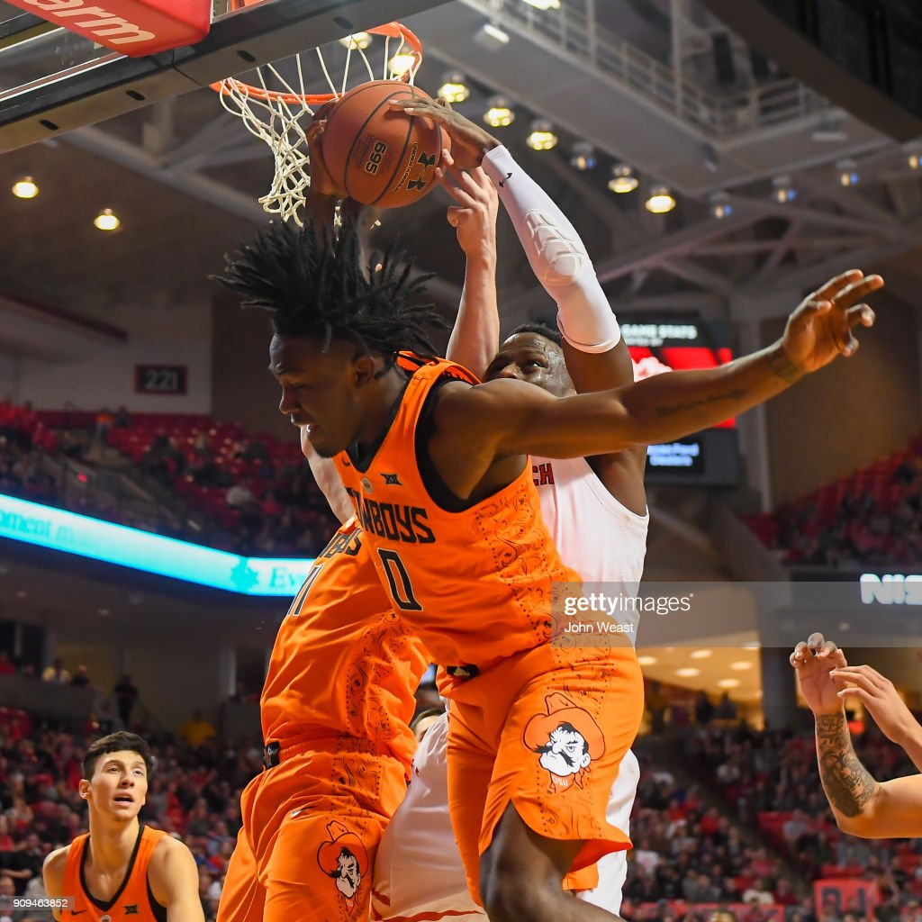 Norense Odiase #32 of the Texas Tech Red Raiders and Brandon Averette #0 of the Oklahoma State Cowboys battle for the rebound during the second half of the game on January 23, 2018 at United Supermarket Arena in Lubbock, Texas. Texas Tech defeated Oklahoma State 75-70.