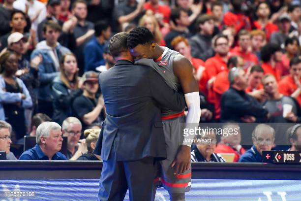 Norense Odiase of the Texas Tech Red Raiders embraces head coach Chris Beard as he leaves the court during the second half of the game on February 16...