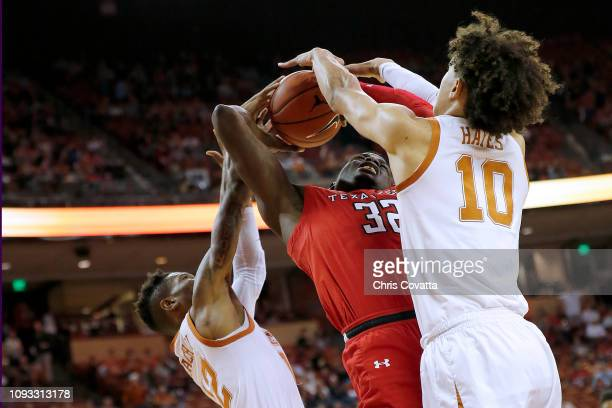 Norense Odiase of the Texas Tech Red Raiders is trapped between Kerwin Roach II and Jaxson Hayes of the Texas Longhorns during first half action at...