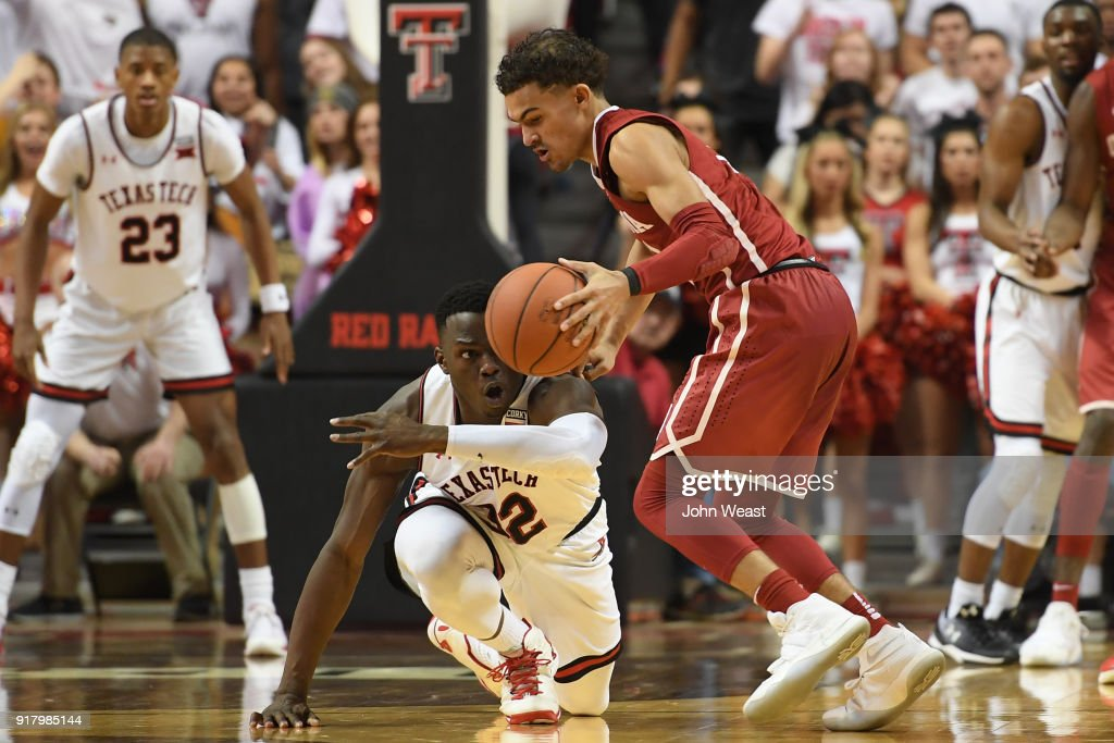 Norense Odiase #32 of the Texas Tech Red Raiders tries to knock the ball away from Trae Young #11 of the Oklahoma Sooners during the second half of the game on February 13, 2018 at United Supermarket Arena in Lubbock, Texas. Texas Tech defeated Oklahoma 88-78.