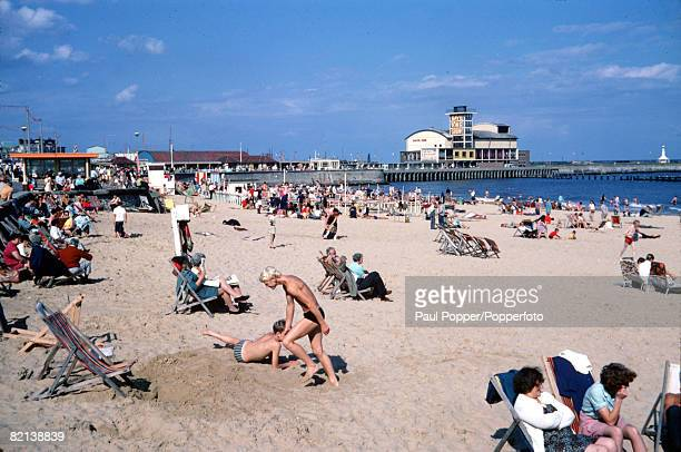 Norfolk England Circa 1980's Holidaymakers enjoy the sun on the beach at Lowestoft as the pier is pictured in the background