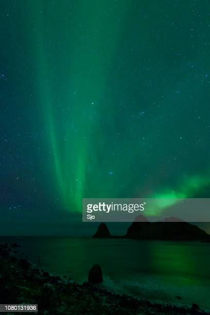 Norhtern Lights or aurora  over the snowy mountains in Northern Norway