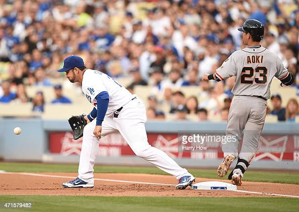 Nori Aoki of the San Francisco Giants beats out a throw for a single in front of Adrian Gonzalez of the Los Angeles Dodgers during the first inning...