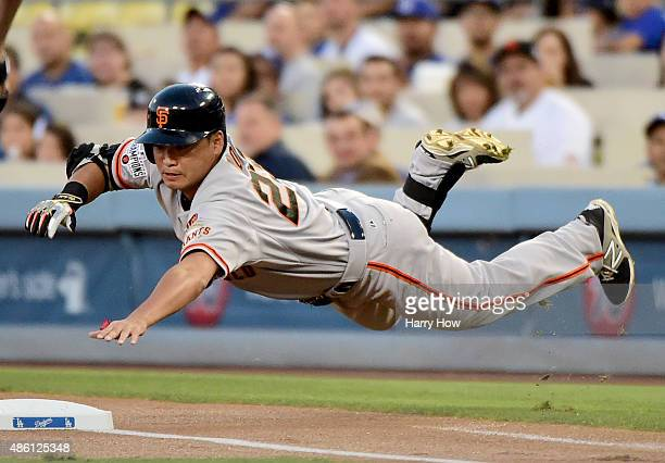Nori Aoki of the San Francisco Giants dives to first base during the first inning against the Los Angeles Dodgers at Dodger Stadium on August 31 2015...