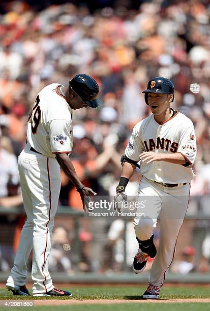 Nori Aoki of the San Francisco Giants is congratulated by third base coach Roberto Kelly after Aoki hit a lead-off solo home run against the Los...