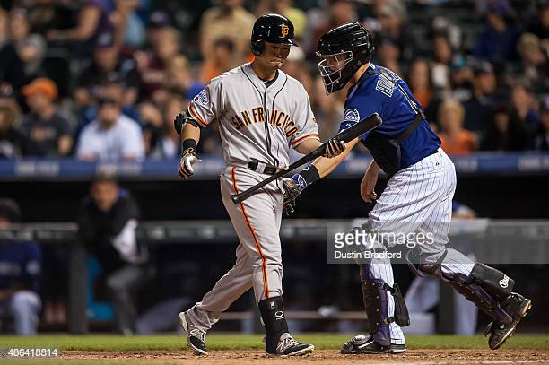 Nori Aoki of the San Francisco Giants is tagged out by Nick Hundley of the Colorado Rockies after striking out in a fifth inning pinch hit appearance...