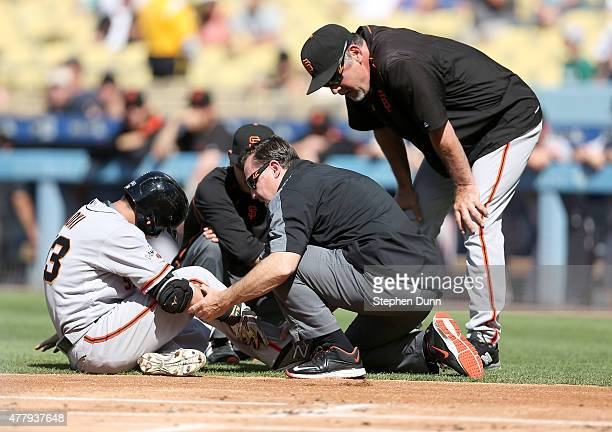 Nori Aoki of the San Francisco Giants is tended to by Giants' trainers as manager Bruce Bochy looks on after Aoki was hit in the ankle by a pitch in...
