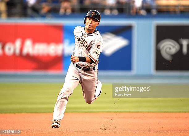 Nori Aoki of the San Francisco Giants runs to third base ahead of a throw on a single by Buster Posey during the first inning against the Los Angeles...