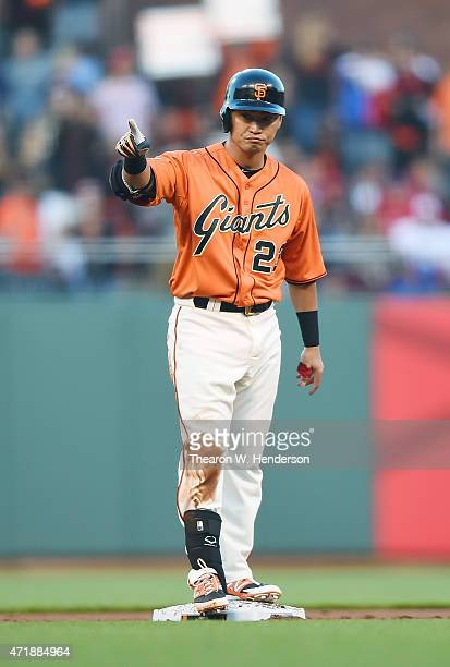 Nori Aoki of the San Francisco Giants stands on second base and points into the dugout after hitting a double against the Los Angeles Angels of...