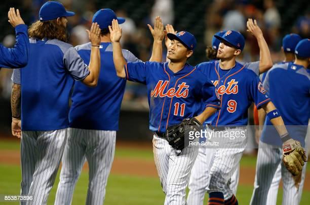 Norichika Aoki and Brandon Nimmo of the New York Mets high fives teammates after defeating the Atlanta Braves 32 during the second game of a...