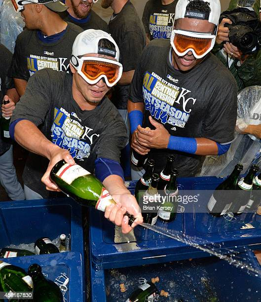 Norichika Aoki and Salvador Perez of the Kansas City Royals spray their teammates with champagne as they celebrate a wild card clinch after defeating...