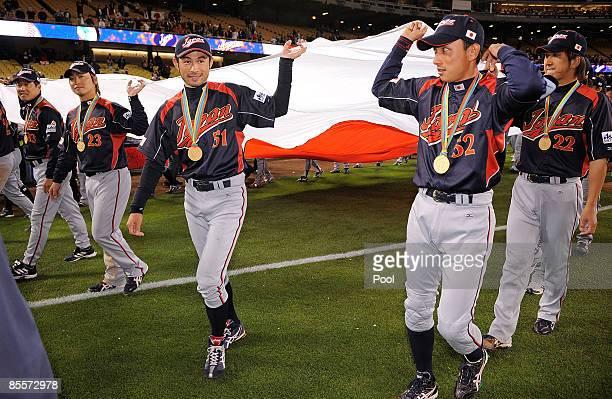 Norichika Aoki Ichiro Suzuki and Munenori Kawasaki of Japan carries the Japanese flag after Japan defeated Korea 53 in the finals of the 2009 World...