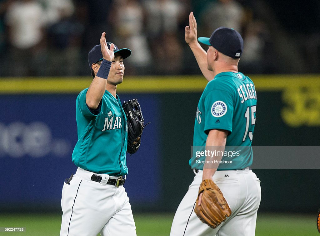 Norichika Aoki #8, left, of the Seattle Mariners and Kyle Seager #15 of the Seattle Mariners celebrate a victory over the Milwaukee Brewers at Safeco Field on August 19, 2016 in Seattle, Washington. The Mariners won the game 7-6.