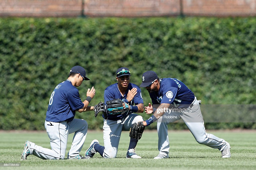Norichika Aoki #8, Leonys Martin #12 and Franklin Gutierrez #21 of the Seattle Mariners celebrate after the final out of the ninth inning against the Chicago Cubs at Wrigley Field on July 30, 2016 in Chicago, Illinois. The Mariners defeated the Cubs 4-1.