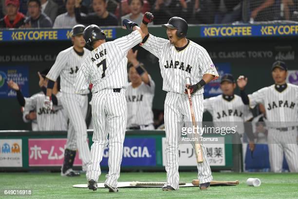 Norichika Aoki of Japan celebrates with his teammates after scoring as Yoshitomo Tsutsugo of Japan hits a RBI single in the first inning of the World...