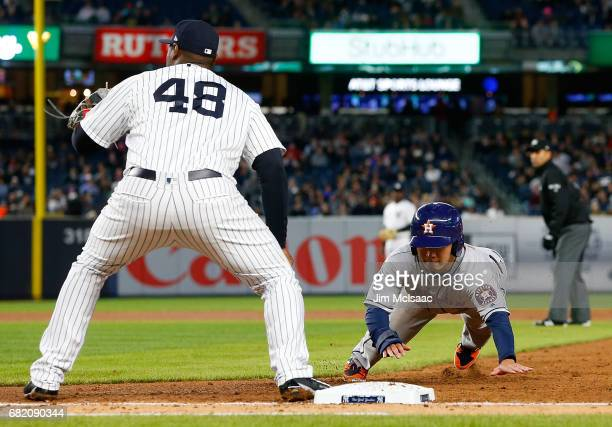 Norichika Aoki of the Houston Astros dives back to first base safely ahead of the throw to Chris Carter of the New York Yankees on a pick off attempt...