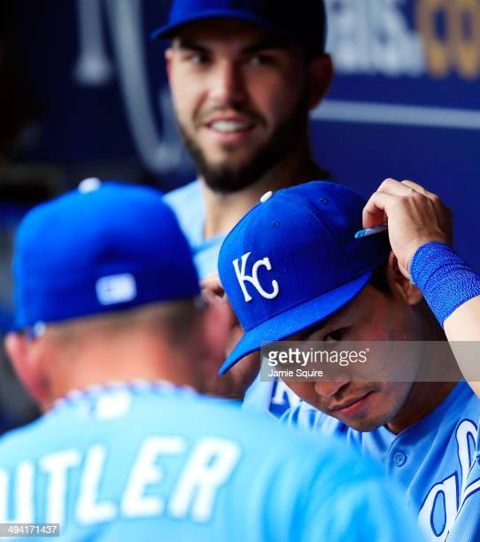 Norichika Aoki of the Kansas City Royals adjusts his sunglasses in the dugout alongside Eric Hosmer and Billy Butler prior to the start of the game...