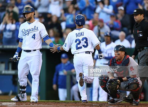 Norichika Aoki of the Kansas City Royals celebrates with Alex Gordon after scoring on a throwing error by Christian Vazquez of the Boston Red Sox on...