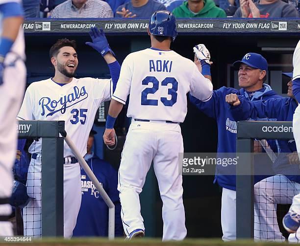 Norichika Aoki of the Kansas City Royals celebrates with Eric Hosmer and manager Ned Yost of the Kansas City Royals after scoring on a throwing error...