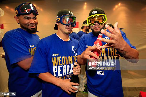 Norichika Aoki of the Kansas City Royals celebrates with teammates Kelvin Herrera and and Francisley Bueno in the locker room after their 2 to 1 win...