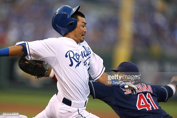 Norichika Aoki of the Kansas City Royals crosses first base as he out runs the throw to Carlos Santana of the Cleveland Indians for a single in the...