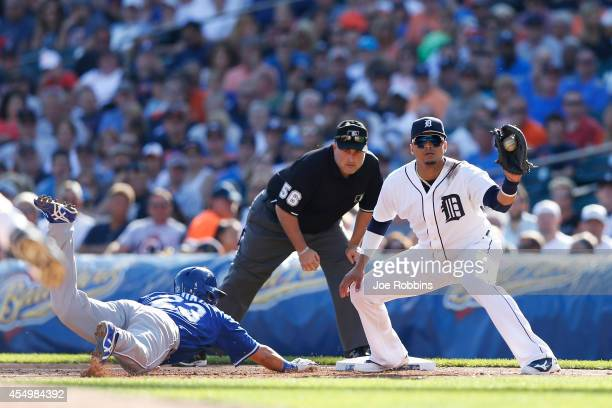 Norichika Aoki of the Kansas City Royals dives back to first base ahead of the throw to Victor Martinez of the Detroit Tigers in the third inning of...