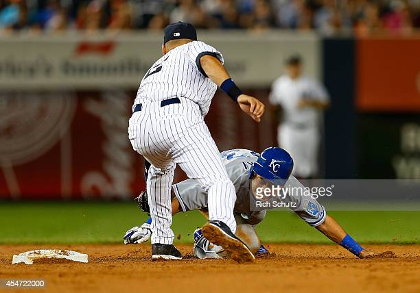 Norichika Aoki of the Kansas City Royals is tagged out by Derek Jeter of the New York Yankees after stealing second base but oversliding past it...