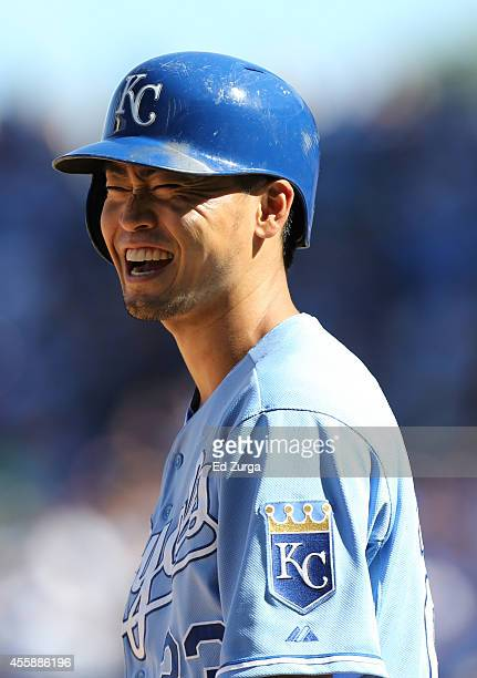 Norichika Aoki of the Kansas City Royals laughs as he stands on third base after hitting a three-run triple in the fourth inning during a game...
