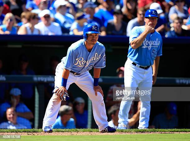 Norichika Aoki of the Kansas City Royals leads off third base as third base coach Mike Jirschele watches after hitting a triple during the 7th inning...