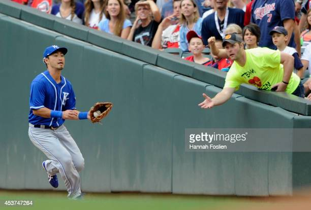 Norichika Aoki of the Kansas City Royals makes a catch in foul territory of the ball hit by Brian Dozier of the Minnesota Twins during the first...