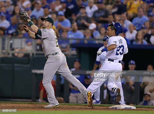 Norichika Aoki of the Kansas City Royals reaches first for a single as Stephen Vogt of the Oakland Athletics waits for the throws in the fifth inning...
