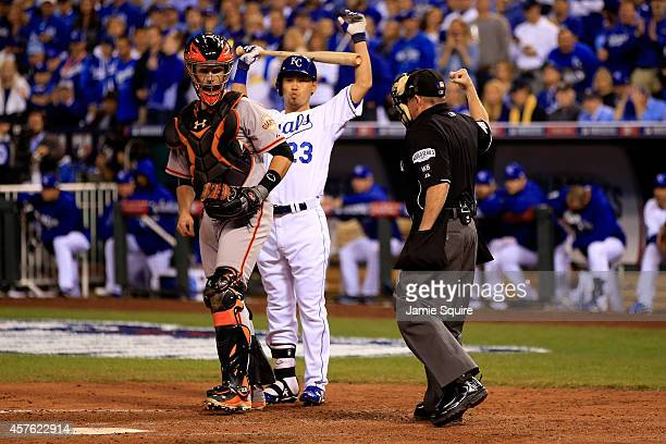 Norichika Aoki of the Kansas City Royals reacts after striking out in the third inning as Buster Posey of the San Francisco Giants look on during...