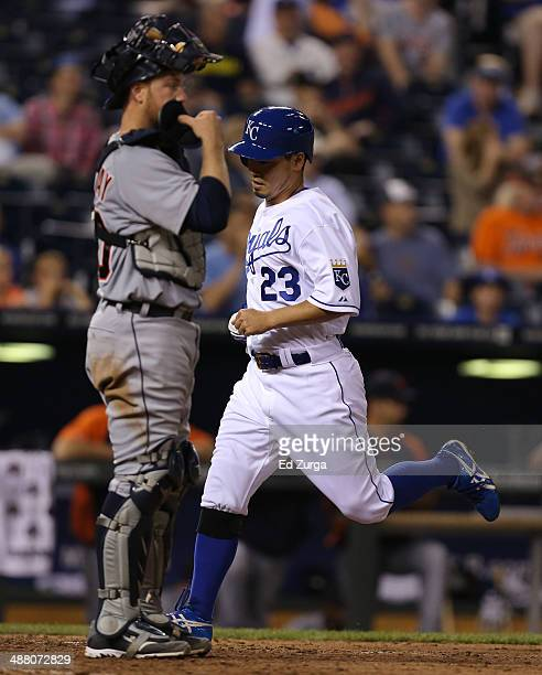 Norichika Aoki of the Kansas City Royals runs past Bryan Holaday of the Detroit Tigers as he scores on a Billy Butler sacrifice fly in the ninth...