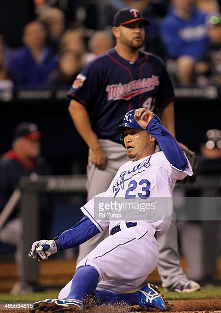 Norichika Aoki of the Kansas City Royals slides into home to score past Ricky Nolasco of the Minnesota Twins in the third inning at Kauffman Stadium...