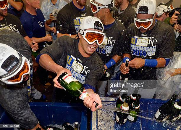 Norichika Aoki of the Kansas City Royals sprays his teammates with champagne as they celebrate a wild card clinch after defeating the Chicago White...
