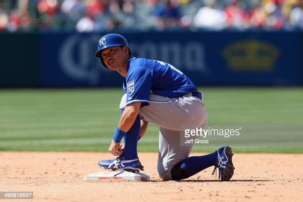Norichika Aoki of the Kansas City Royals ties his shoe at second base after coming into the game against the Los Angeles Angels of Anaheim as a pinch...