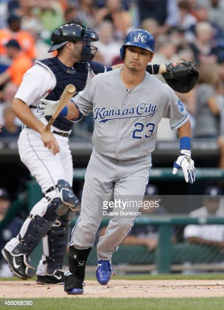 Norichika Aoki of the Kansas City Royals tosses down his bat as he heads for first base on a walk as catcher Alex Avila of the Detroit Tigers directs...