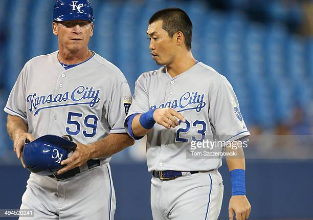 Norichika Aoki of the Kansas City Royals walks off the field with third base coach Mike Jirschele at the conclusion of the first inning during MLB...