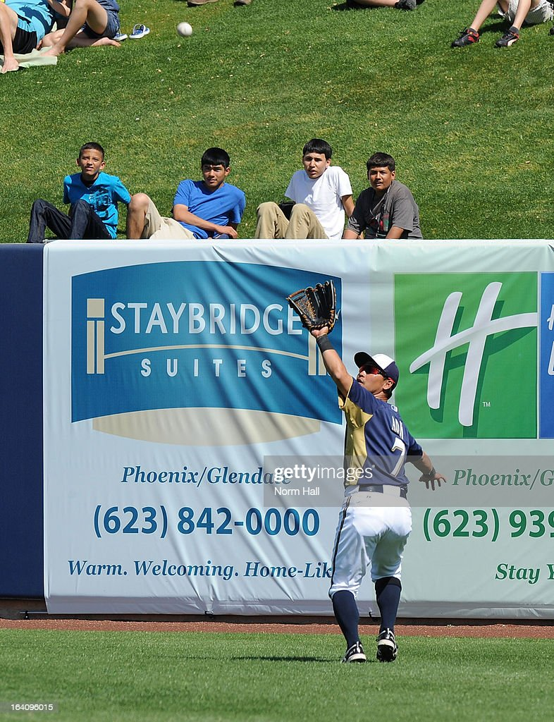 Norichika Aoki #7 of the Milwaukee Brewers catches a fly ball just in front of the right field wall against the Los Angeles Angels of Anaheim at Maryvale Baseball Park on March 19, 2013 in Maryvale, Arizona.