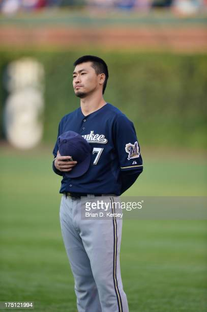 Norichika Aoki of the Milwaukee Brewers stands on the field for the singing of 'The Star Spangled Banner' against the Chicago Cubs at Wrigley Field...
