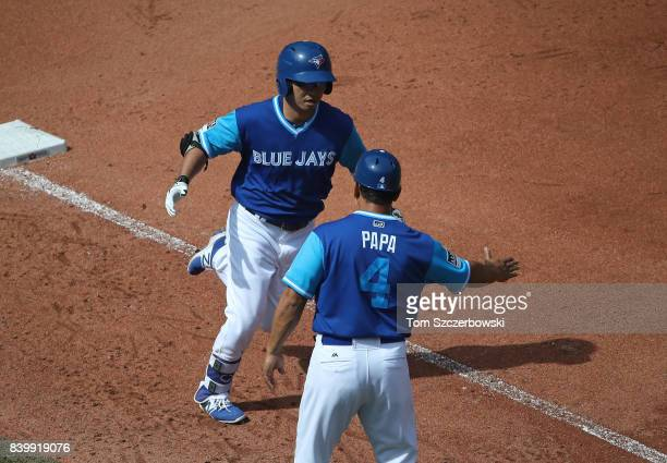 Norichika Aoki of the Toronto Blue Jays is congratulated by third base coach Luis Rivera after hitting a solo home run in the fourth inning during...