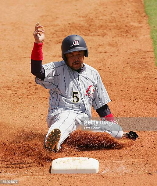 Norihiro Nakamura of Japan safely slides into third base during their game against Greece during the baseball preliminary game on August 22 2004...