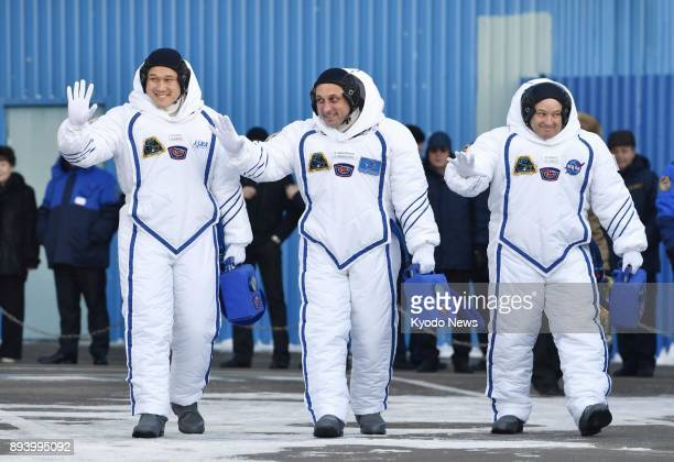 Norishige Kanai of Japan Anton Shkaplerov of Russia and Scott Tingle of the United States wave to onlookers before boarding a Soyuz spacecraft in...