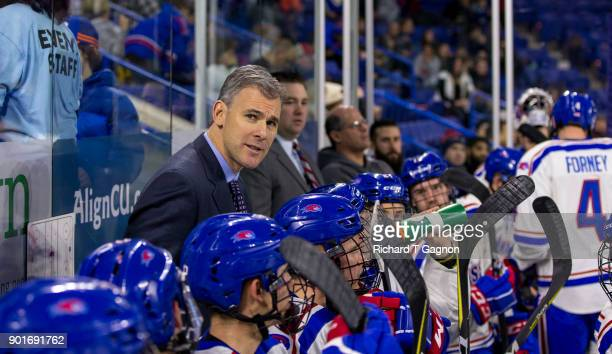 Norm Bazin head coach of the Massachusetts Lowell River Hawks stands behind the bench during NCAA men's hockey against the Vermont Catamounts at the...