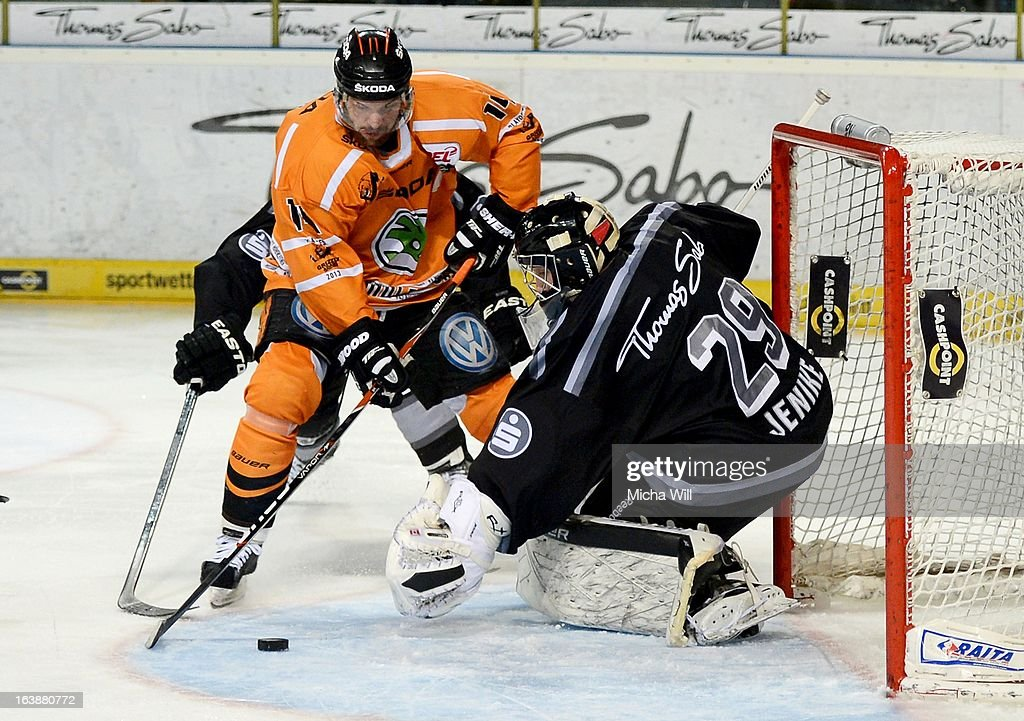 Norm Milley (L) of Wolfsburg scores the first goal for his team against goalie Andreas Jenike of Nuremberg during game three of the DEL pre-play-offs between Thomas Sabo Ice Tigers and Grizzly Adams Wolfsburg on March 17, 2013 in Nuremberg, Germany.