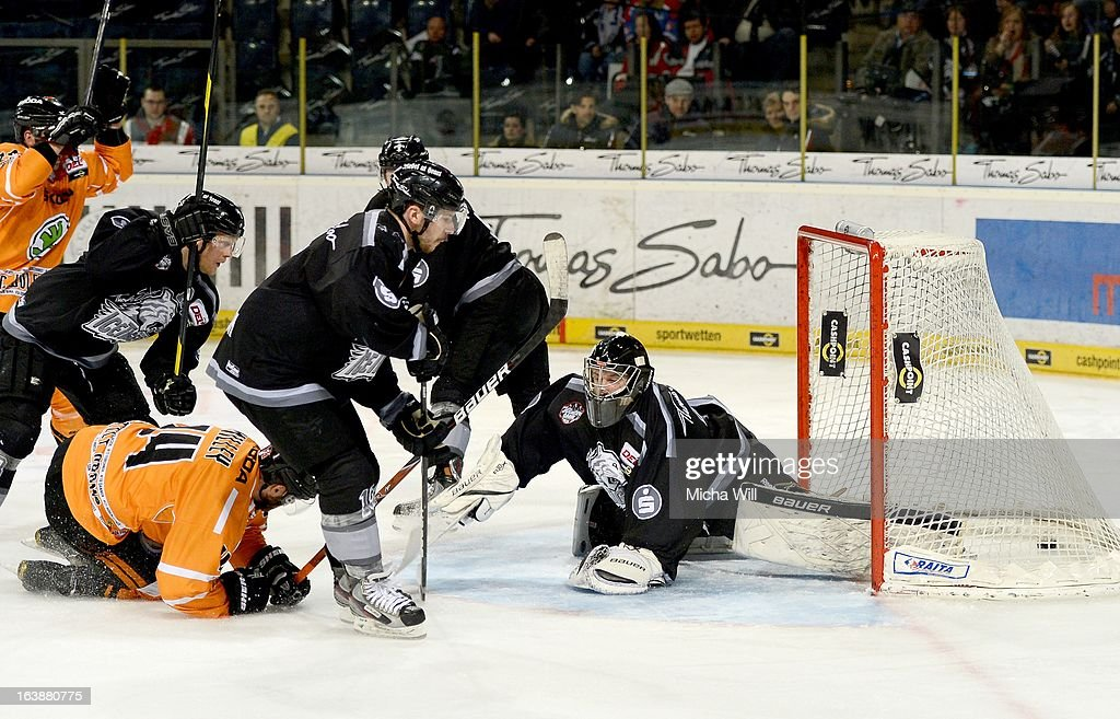 Norm Milley (front L) of Wolfsburg scores the first goal for his team during game three of the DEL pre-play-offs between Thomas Sabo Ice Tigers and Grizzly Adams Wolfsburg on March 17, 2013 in Nuremberg, Germany.