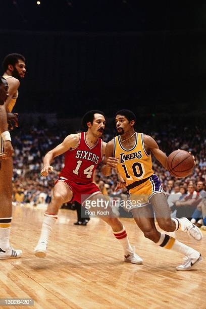 Norm Nixon of the Los Angeles Lakers dribbles against Chris Ford of the Philadelphia 76ers during a game played circa 1987 at the Great Western Forum...
