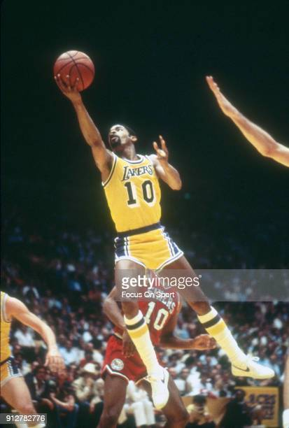 Norm Nixon of the Los Angeles Lakers goes in for a layup over Maurice Cheeks of the Philadelphia 76ers during an NBA basketball game circa 1978 at...