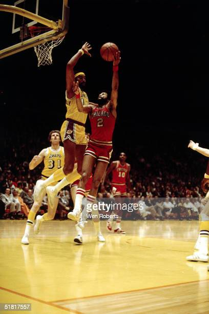 Norm Van Lier of the Chicago Bulls shoots a hookshot against Wilt Chamberlain of the Los Angeles Lakers during an NBA game circa 1973 at the Forum in...